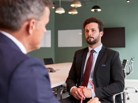 A man interviewing another male about prospective employment